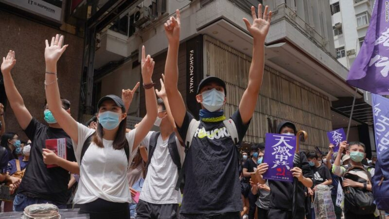 """Protesters gesture with five fingers, signifying the """"Five demands - not one less"""" as they march along a downtown street during a pro-democracy protest against Beijing's national security legislation in Hong Kong, Sunday, May 24, 2020. Hong Kong's pro-democracy camp has sharply criticised China's move to enact national security legislation in the semi-autonomous territory. They say it goes against the """"one country, two systems"""" framework that promises the city freedoms not found on the mainland."""
